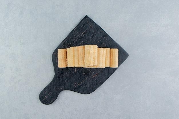 Ein schwarzes holzbrett voller knuspriger waffelröllchen.