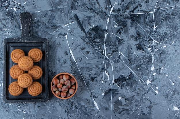 Ein schwarzes holzbrett von süßen frischen runden keksen für tee mit gesunden nüssen auf einem marmorhintergrund.