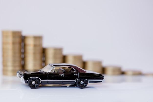 Ein schwarzes modell eines autos mit münzen in form eines histogramms