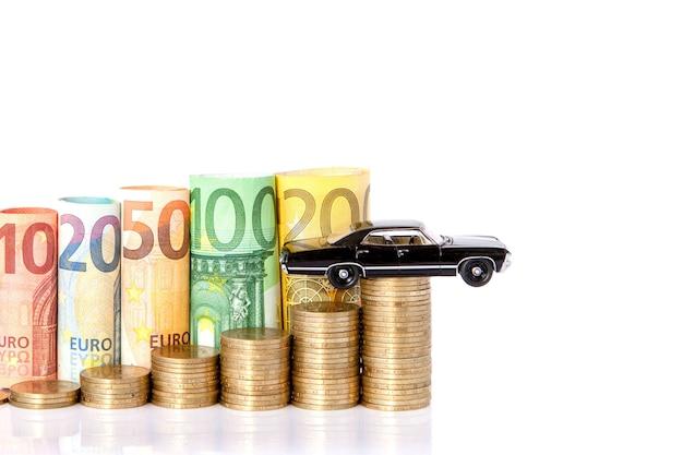 Ein schwarzes modell eines autos und zehn, zwanzig, fünfzig, einhundert, zweihundert und münzen euro rollte banknoten auf weißem hintergrund. histogramm aus dem euro. konzept des währungswachstums, einsparungen.