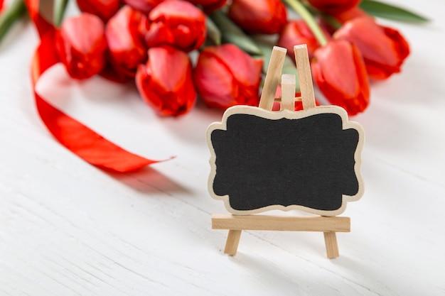 Ein schwarzes schild gegen eine der roten tulpen auf weißem tisch. das konzept des muttertags. speicherplatz kopieren.