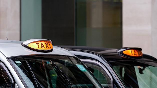 Ein schwarzes taxischild des britischen london mit defokussierten gebäuden