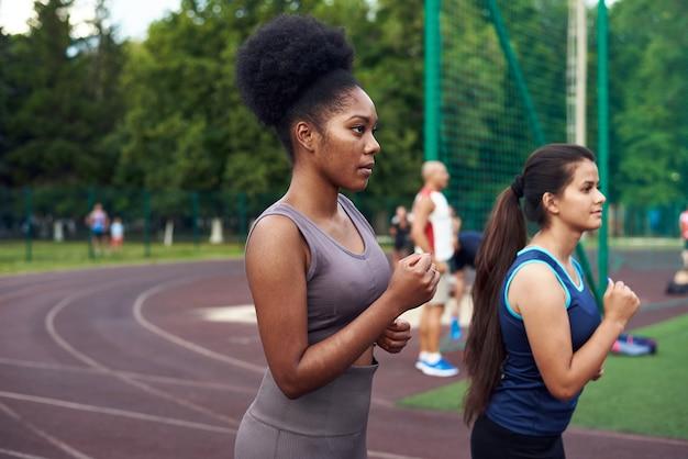 Ein schwarzes und kaukasisches mädchen, das an einem bestimmten ort auf der straße joggt.