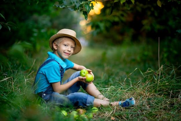 Ein sechsjähriger junge sitzt im gras in einem apfelgarten und hält einen apfel in den händen
