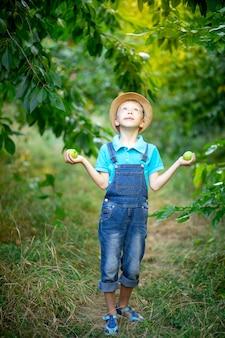 Ein sechsjähriger junge steht in einem blauen kleid und hut in einem garten mit apfelbäumen, die nach oben schauen und äpfel in seinen händen halten