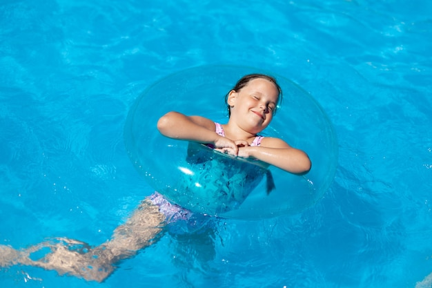 Ein sechsjähriges mädchen genießt ein schwimmbad, einen aufblasbaren kreissommer und einen familienurlaub