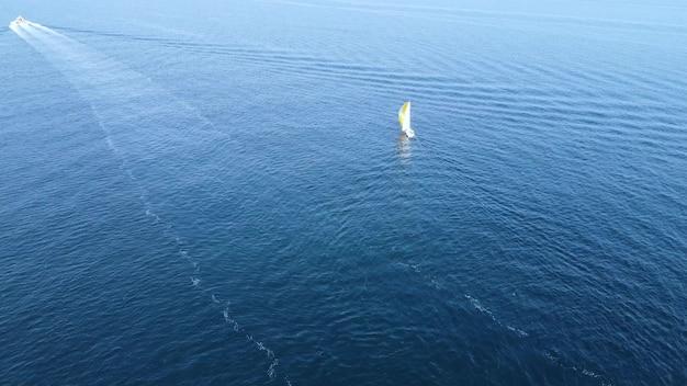 Ein segelboot segelt ins offene meer. luftdrohne aus der vogelperspektive eines schönen weißen segelboots, das auf dem offenen meer verkehrt.