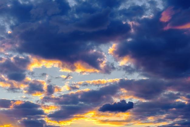 Ein sehr dramatischer himmel voller gelb-, blau- und orangetöne. kontrastierende wolken während des sonnenuntergangs, die von der untergehenden sonne beleuchtet werden. heller gesättigter natürlicher hintergrund. foto in hoher qualität