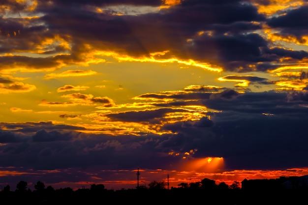 Ein sehr dramatischer himmel voller gelber blau- und orangenkontrastwolken während des sonnenuntergangs, beleuchtet von der untergehenden sonne, hell gesättigt natürlich
