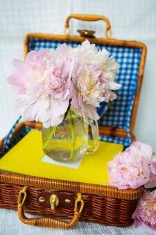 Ein sehr schöner strauß rosa pfingstrosen steht in einer vase auf einem holzkoffer.