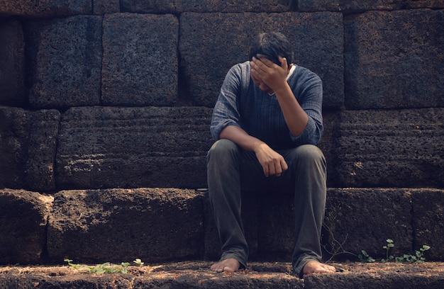 Ein sehr trauriger und depressiver mann, der in der nähe einer wand sitzt Premium Fotos
