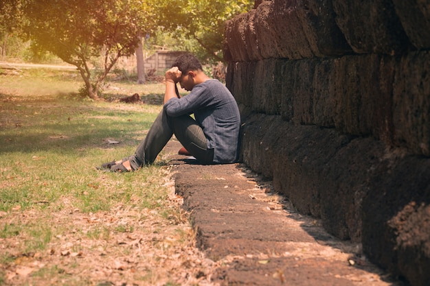 Ein sehr trauriger und depressiver mann, der in der nähe einer wand sitzt