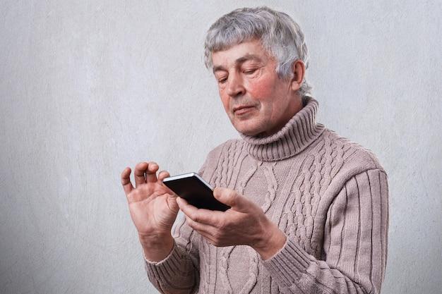 Ein seitliches porträt des reifen mannes, der falten und graues haar im pullover gekleidet hält, der smartphone in seinen händen hält, das buch online liest