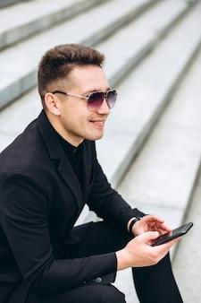 Ein selbstbewusster geschäftsmann durchsucht e-mails auf einem mobiltelefon. stilvolles männliches model in schwarzer jacke. junger mann mit einem handy, das auf den stufen sitzt