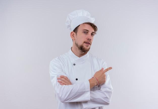 Ein selbstbewusster hübscher junger bärtiger kochmann, der weiße kochuniform und einen hut trägt, der oben zeigt, während er auf eine weiße wand schaut