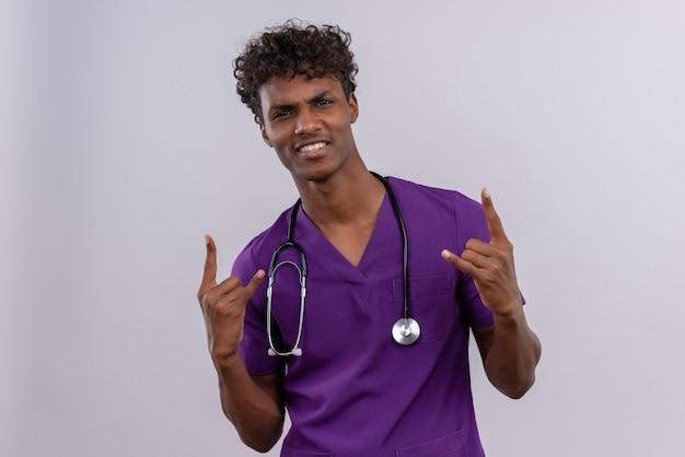 Ein selbstbewusster junger gutaussehender dunkelhäutiger arzt mit lockigem haar in violetter uniform und stethoskop-händchenhalten in der felsgeste
