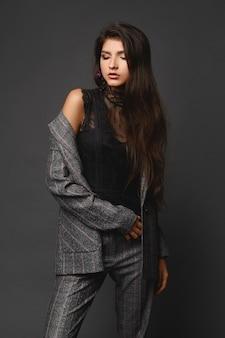 Ein selbstbewusstes model-mädchen mit langen, schönen haaren in einem modisch karierten anzug auf grauem hintergrund, business-modekonzept.