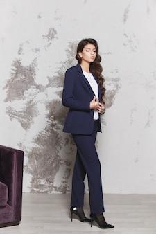Ein selbstbewusstes model-mädchen mit langen schönen haaren in einem stylischen blauen anzug und einer weißen bluse. geschäftsmodekonzept