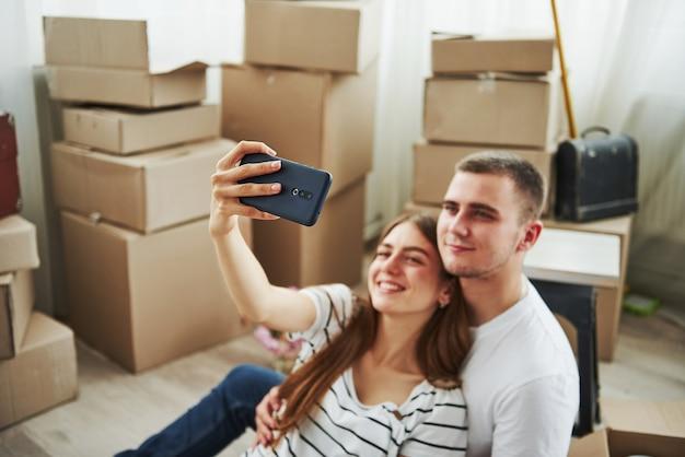 Ein selfie machen. fröhliches junges paar in ihrer neuen wohnung. konzeption des umzugs.