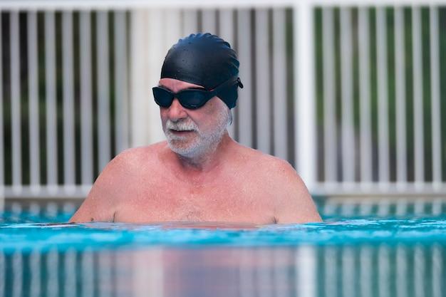 Ein senior am pool trainiert allein, um morgens oder nachmittags gesund zu sein - aktiver reifer mann, der mit brille im blauen wasser schwimmt