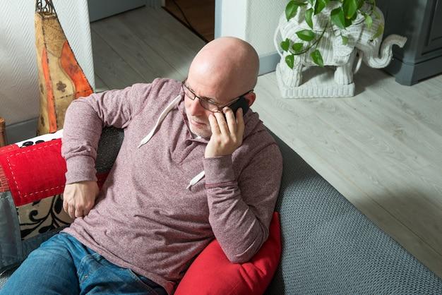 Ein senior mit einem telefon sitzt auf dem sofa