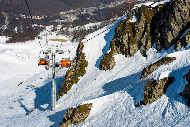 Ein sessellift in den bergen hebt touristen, skifahrer und snowboarder im winter den hang hinauf