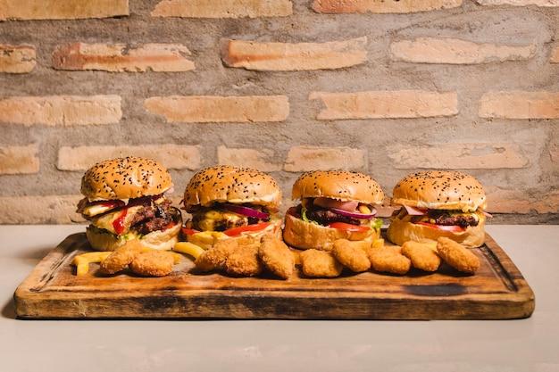 Ein set mit vier köstlichen hamburgern unterschiedlicher größe, die rundum mit nuggets gefüllt sind