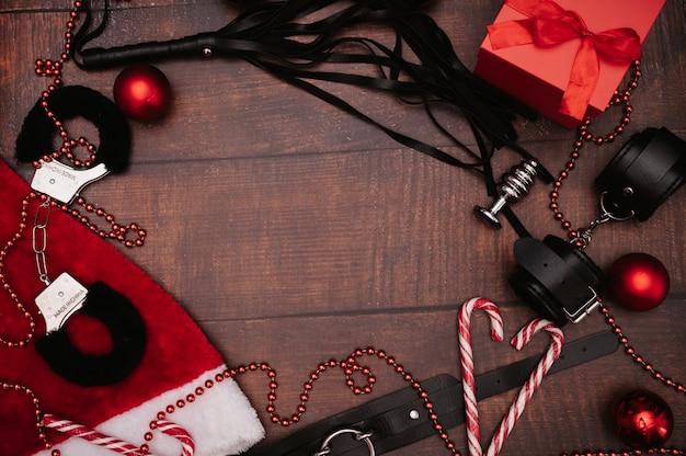 Ein set von bdsm-spielzeug für erwachsene mit weihnachtsdekor. ein rahmen mit platz für text. flatley. beispiel für ein geschenk. handschellen, peitsche, analplug, weihnachtskugeln.