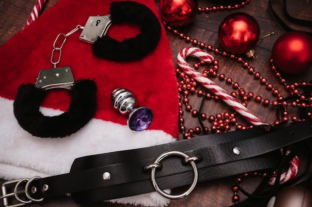 Ein set von bdsm-spielzeug für erwachsene mit weihnachtsdekor. flatley. handschellen, peitsche, analplug, weihnachtskugeln.