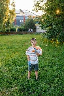 Ein siebenjähriger junge ist bei sonnenuntergang mit der müllabfuhr im park beschäftigt. umweltschutz, recycling.