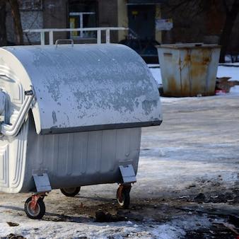 Ein silberner abfallbehälter steht im winter in der nähe von wohngebäuden