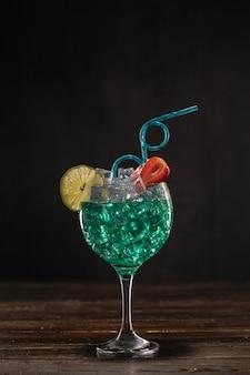Ein smaragdfarbener cocktail in einem eisglas, dekoriert mit limette und erdbeeren mit einem lockigen trinkhalm