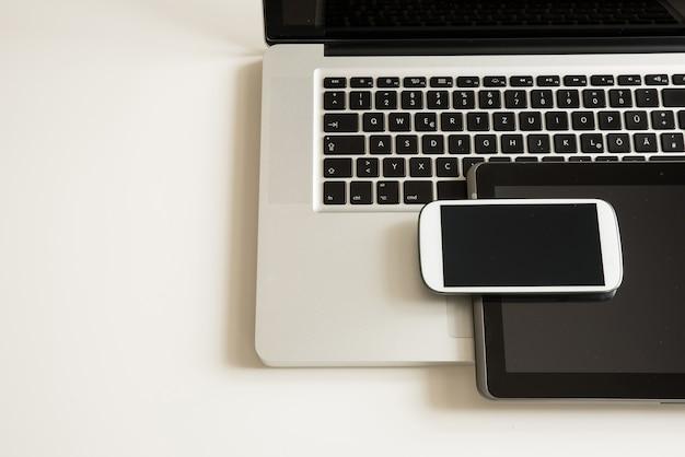 Ein smartphone, ein laptop und ein tablet pc zusammen auf einem desktop.