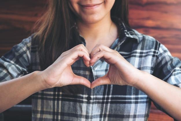Ein smiley asiatische frau machen herz handzeichen mit gefühl inlove