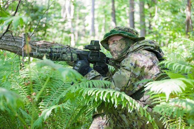 Ein soldat im wald bei der übung. maschinengewehr und kleidung des soldaten