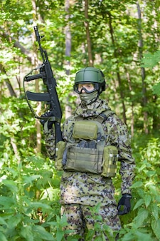 Ein soldat im wald mit einem maschinengewehr in friedenszeiten. vorbereitung des militärs auf feindseligkeiten.