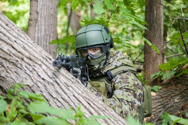 Ein soldat im wald sitzt im hinterhalt. maschinengewehr und kleidung des soldaten