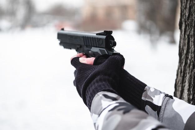 Ein soldat in tarnung und handschuhen zielt mit einer pistole neben einen baum.