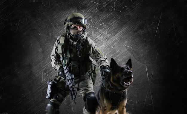 Ein soldat in uniform mit einer waffe in der hand setzt den schäferhund auf einen verbrecher. gemischte medien