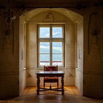 Ein solitärstuhl und ein tisch in einem geräumigen raum des schlosses savoia, gebäude im typischen walsen-baustil.
