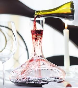 Ein sommelier, der rotwein in dekanter gießt