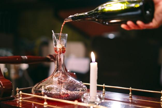 Ein sommelier, der rotwein in die karaffe gießt