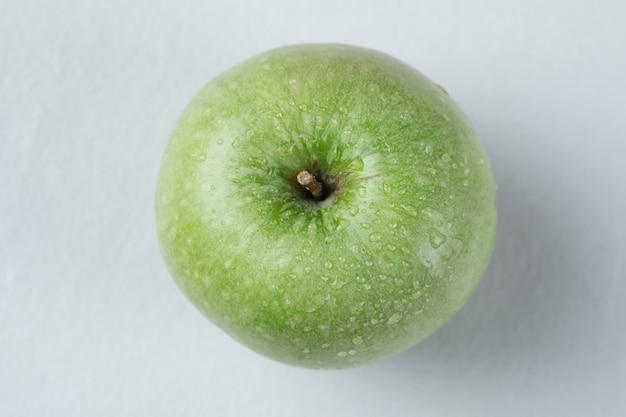 Ein songle grüner apfel isoliert auf grau.