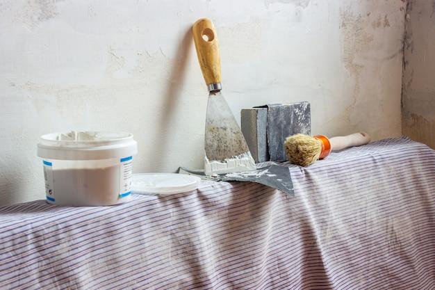 Ein spachtel, ein pinsel, sandpapier und eine wandversiegelungspaste auf einem heizkörper, die bereit sind, die wände zu renovieren. drinnen.