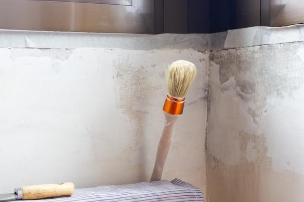 Ein spachtel und ein pinsel auf einem heizkörper sind bereit, die wand zu befestigen