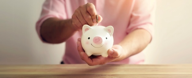 Ein sparschwein mit hand, die geldmünze auf hölzernen hintergrund setzt. ein sparsames geld für das zukünftige investitionskonzept.