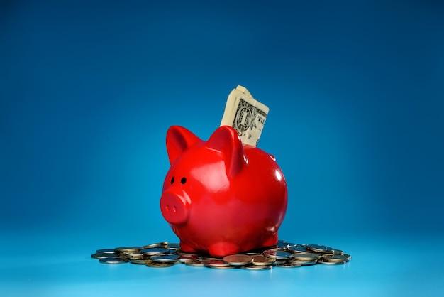 Ein sparschwein sitzt auf einem stapel münzen. familienbudget-konzept.