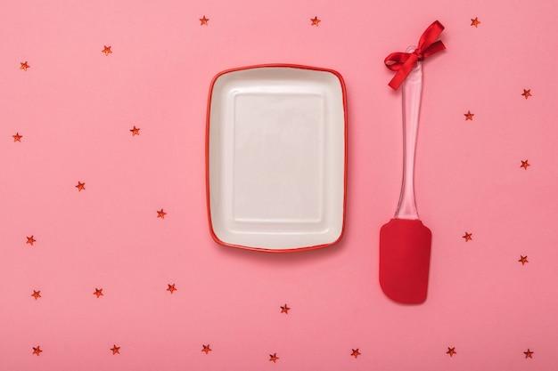 Ein spatel mit rotem band und eine schüssel auf rosafarbenem hintergrund mit leuchtenden sternen. küchengeräte auf festlichem hintergrund. flach liegen.