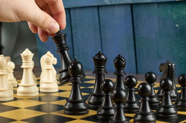 Ein spieler, der schwarze figuren auf schachbrett spielt