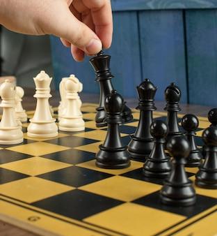 Ein spieler, der schwarzen könig auf schachbrett spielt